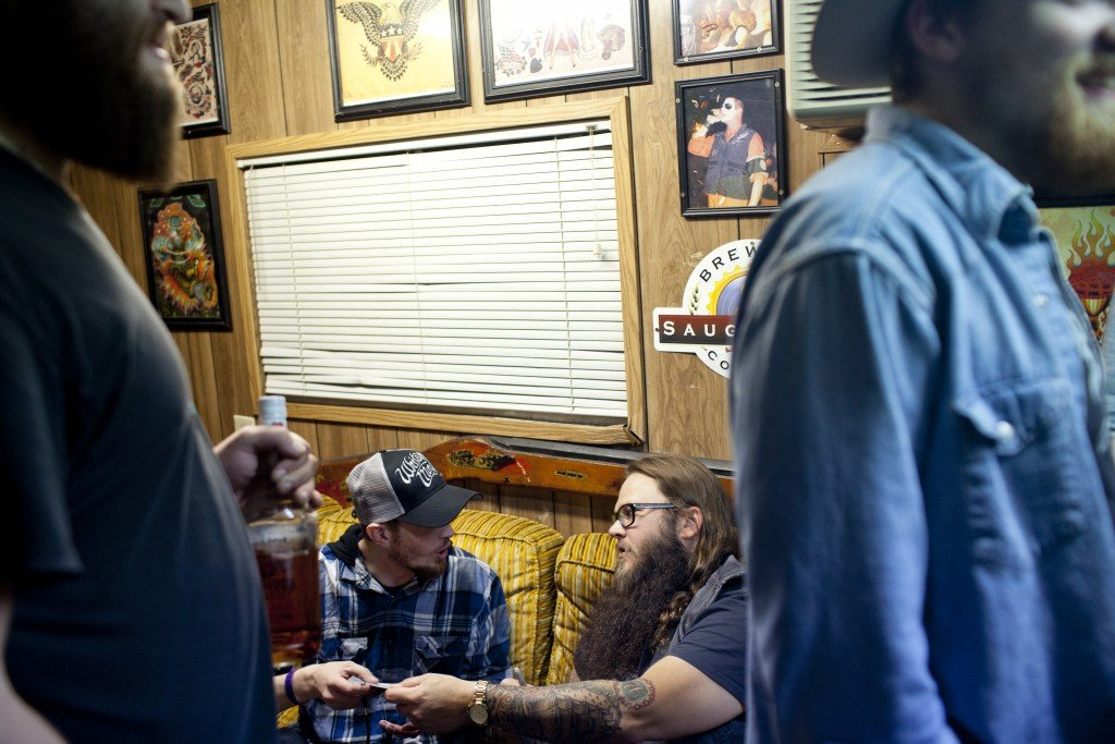 Flint native Whitey Morgan gives his latest CD to a fan during a VIP greeting session backstage before a show at The Machine Shop in Flint, MI on May 1, 2015.