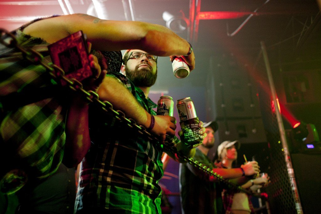 Fans hold beers and lean over a chain barrier while watching the Whitey Morgan and the 78's show at The Machine Shop in Flint, MI on May 1, 2015.