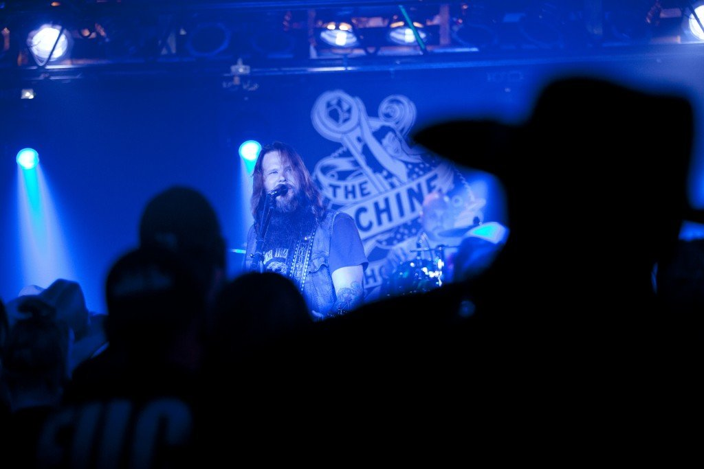 Flint native Whitey Morgan is bathed in blue stage light as he is seen through the audience members during a show at The Machine Shop in Flint, MI on May 1, 2015.