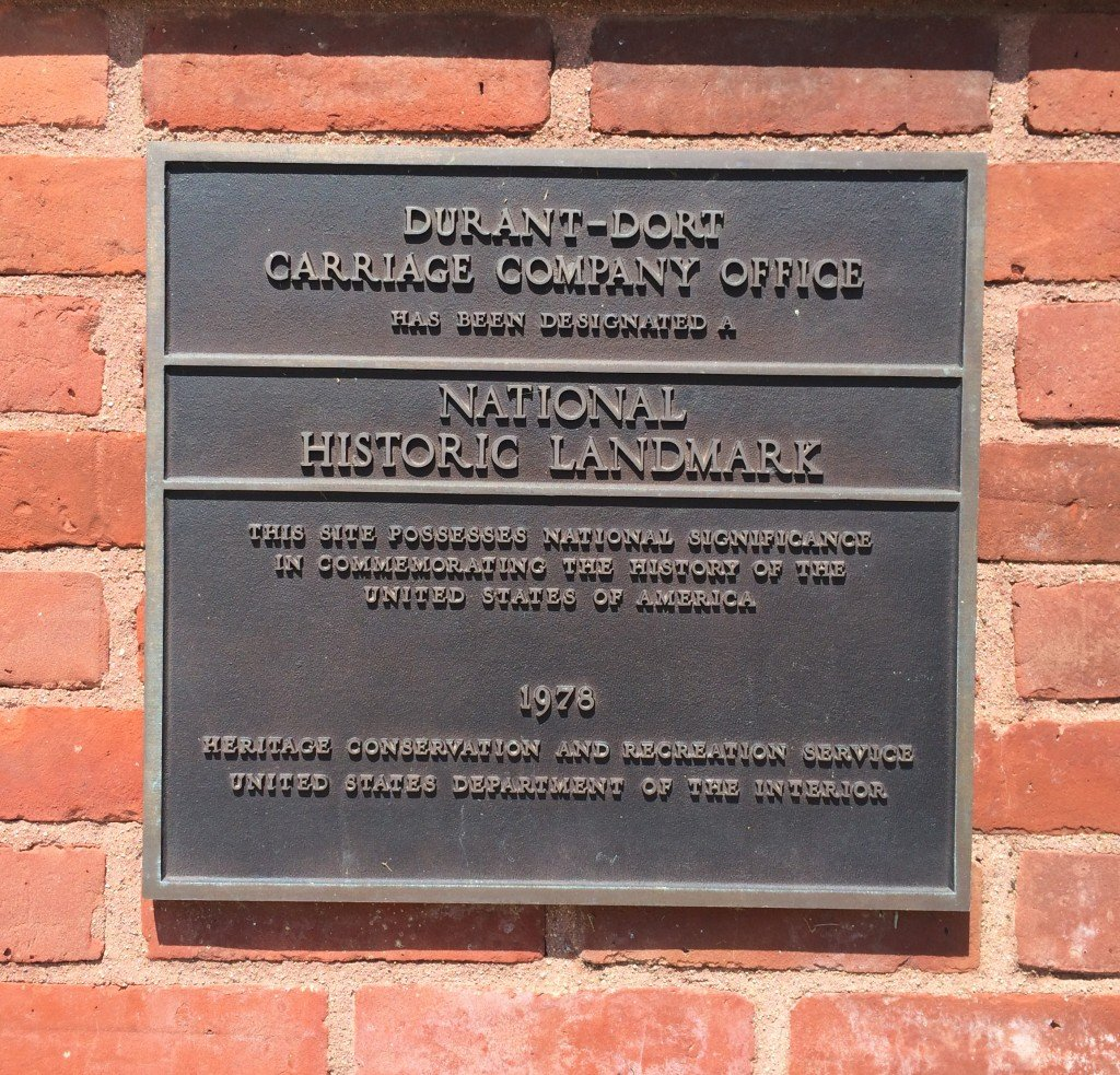 """A plaque on the Durant-Dort Carriage Co. -- the company that would in time lead to the formation of General Motors under William """"Billy"""" Durant -- shows off its status as a historic landmark."""