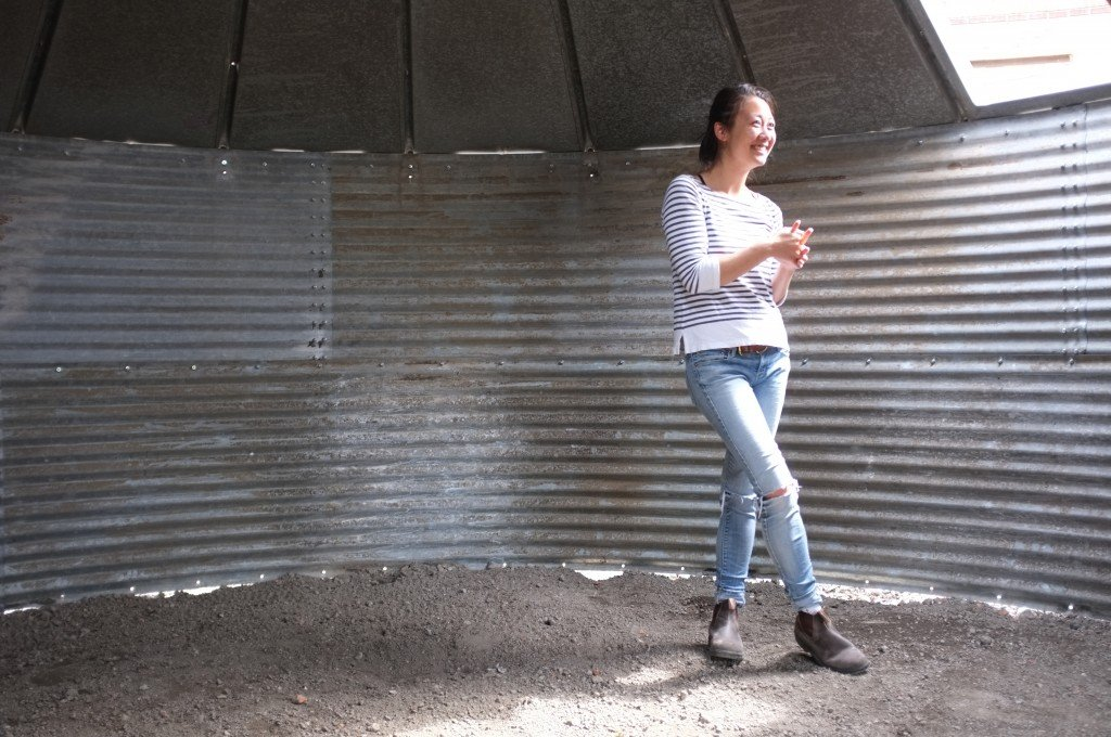 Gallery Director Alison Wong stands inside an under-construction art display at Wasserman Projects. When completed, the structure — a grain silo in the shape of a yurt — will play different sounds and music depending on how many people are in the space, what they touch, and where they stand or sit.