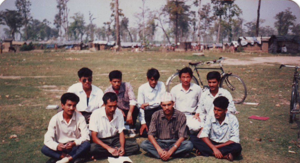 Naresh in the second row, second from the left, with his colleagues as a volunteer teacher in the refugee camps in Nepal (1992/1993). In the background are rows after rows of huts made out of bamboos with thatched roofs or tarpaulins.