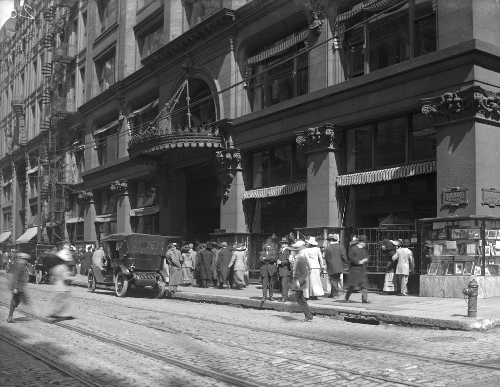 A view of Smithfield Street at Diamond Street, showing a crowd of people walking by Kaufmann's Department Store.