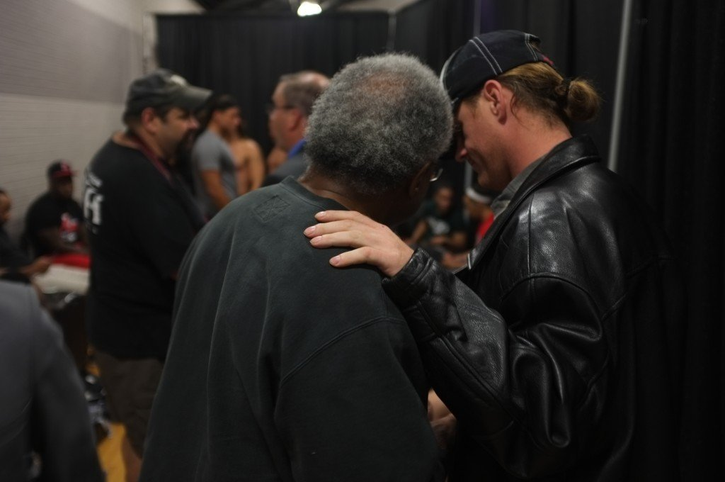 Leo Napier, also known as the wrestler Father Time (left), talks with his coach Joe Byrd after his debut match with the Ring of Honor.