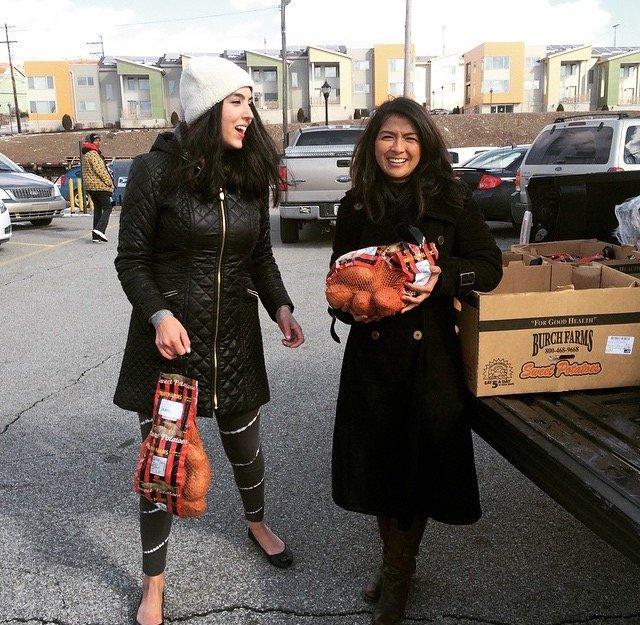 Gisele Fetterman (l) and Leah Lizarondo (r) rescue some donated sweet potatoes.